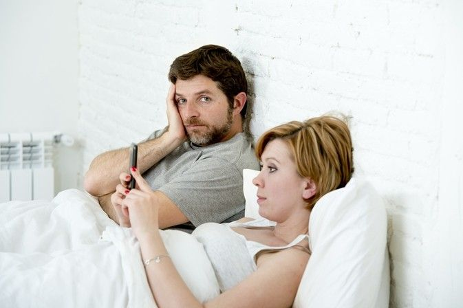 couple in bed woman on phone